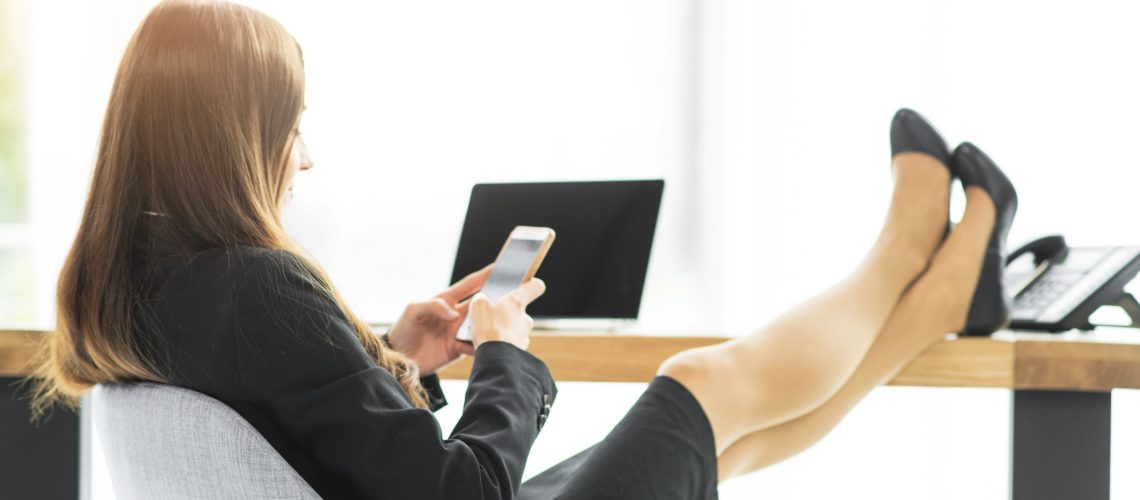 businesswoman-relaxing-at-desk-using-smartphone-in-the-office