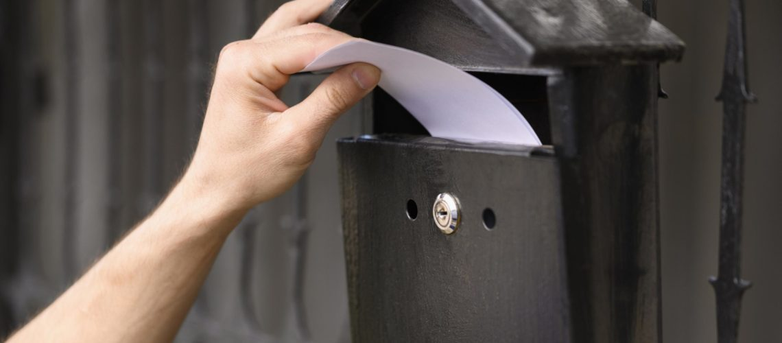 close-up-delivery-man-dropping-envelope-mailbox